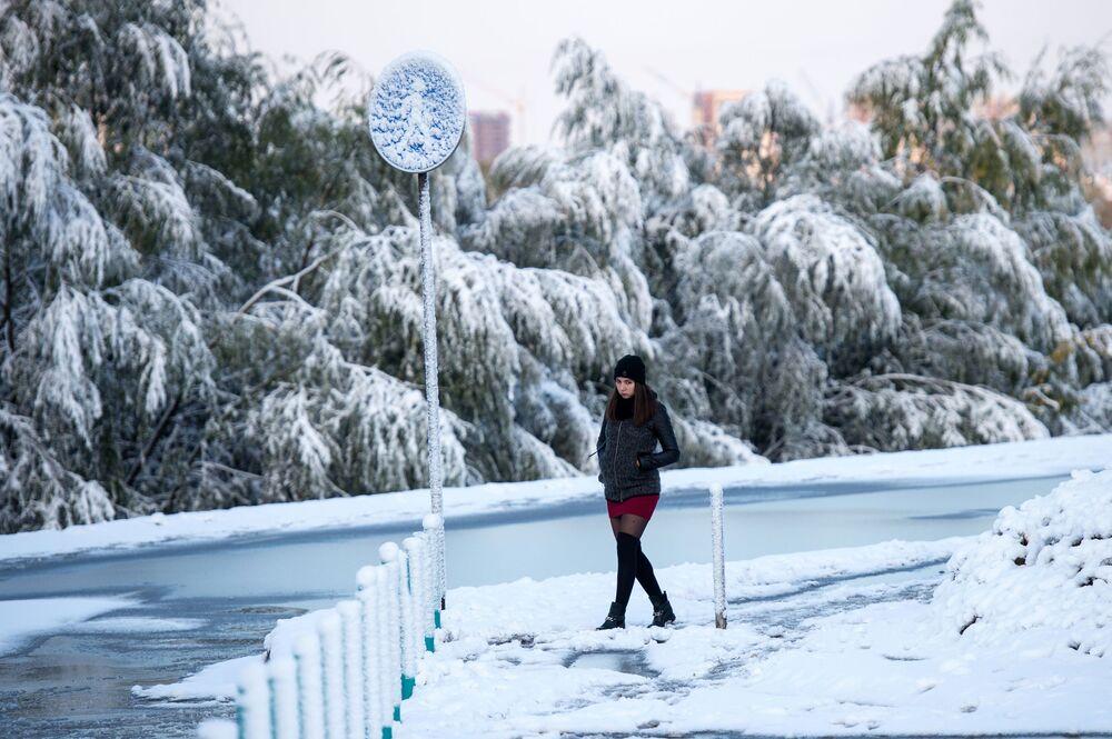 Dziewczyna podczas śnieżnej pogody na ulicy Omska