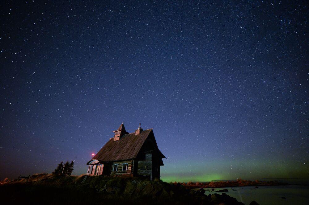 Dom na tle zorzy polarnej nad miasteczkiem Raboczeostrowsk