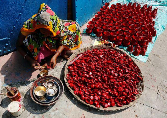 Kobieta maluje lampy gliniane w Kalkucie, Indie