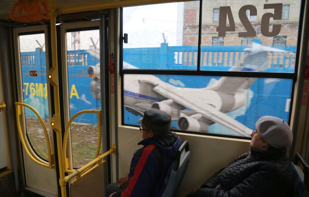 Pasażerowie tramwaju jadą obok graffiti poświęconemu historii rosyjskiego lotnictwa