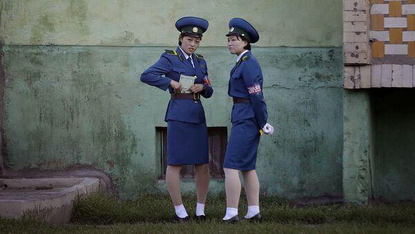 Pracownicy drogówki przed budynkiem w Pjongjangu - Sputnik Polska
