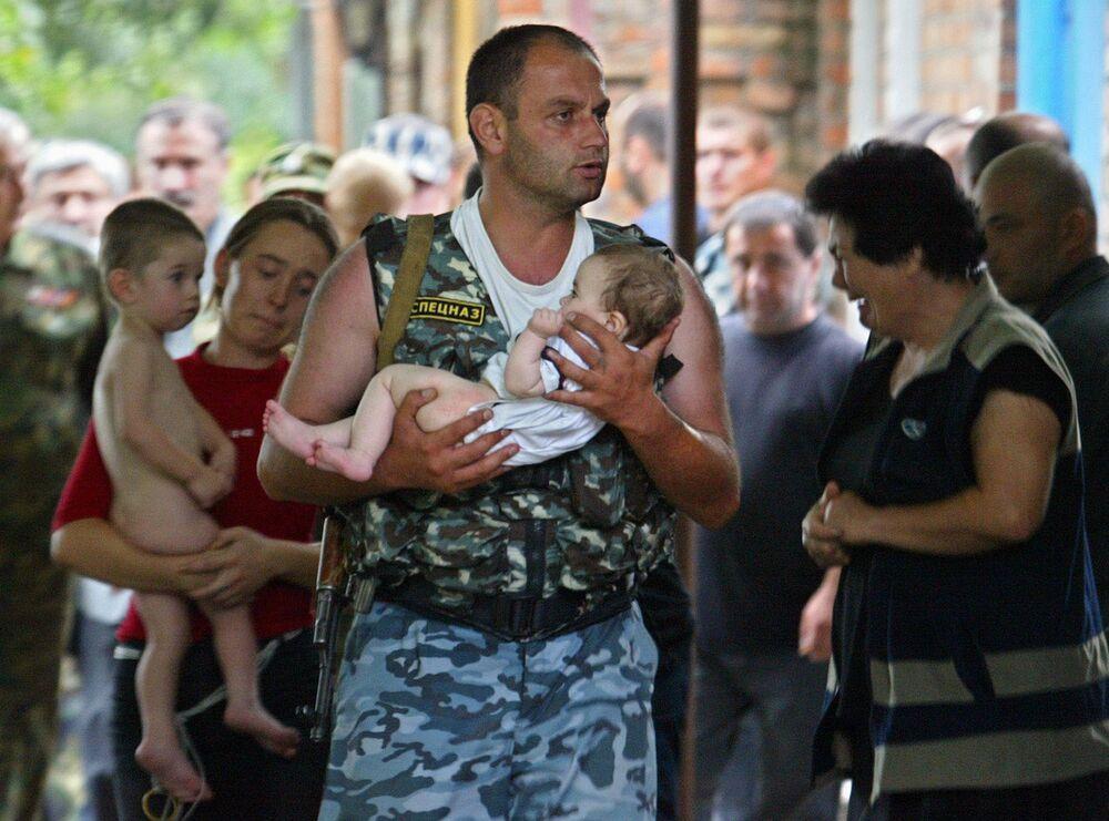 Komandos niesie dziecka po wyzwoleniu szkoły w Biesłanie od terrorystów