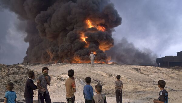 FILE -- In this Sunday, Oct. 23, 2016 file photo, people watch a burning oil well in Qayyarah, about 31 miles (50 km) south of Mosul, Iraq - Sputnik Polska