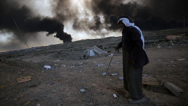 Uchodźca w tle eksplozji podczas operacji irackiej armii przeciwko PI w Mosulu - Sputnik Polska