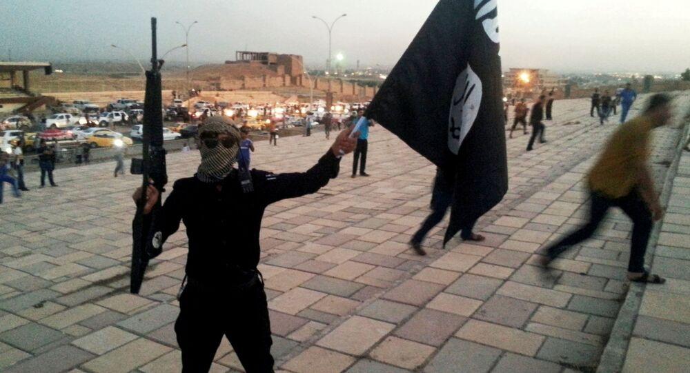 Członek organizacji terrorystycznej PI z flagą na ulicy Mosulu w Iraku