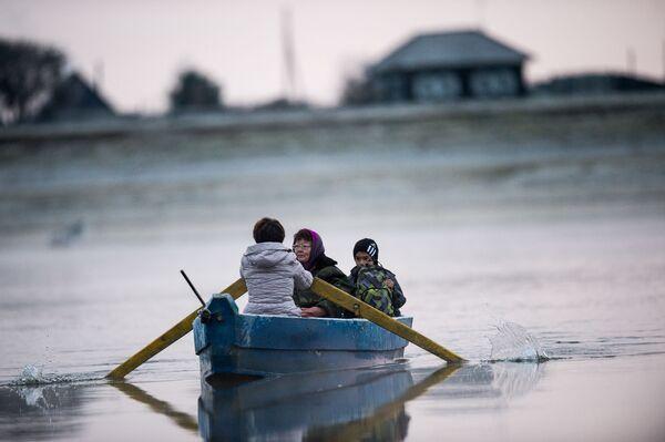 Gulnara Kołdaszewa, matka Ajdara, przewozi syna łodzią na drugi brzeg rzeki Irtysz - Sputnik Polska