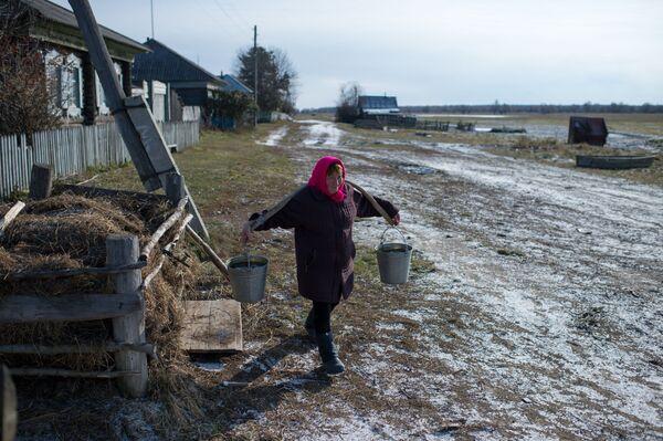 Mieszkanka wsi Sibiliakowo w obwodzie omskim idzie po wodę - Sputnik Polska