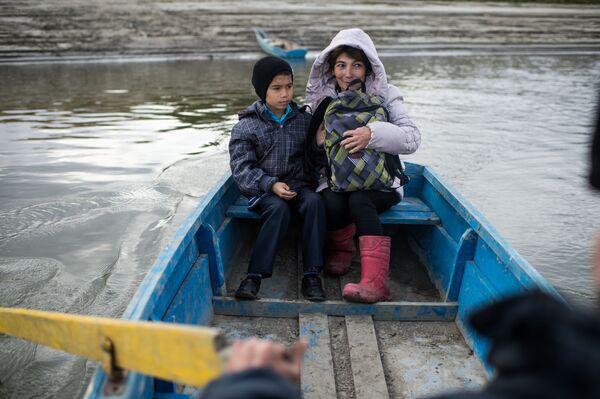 Ajdar Kołdaszew po zajęciach przeprawia się wraz z mamą Gulnarą łodzią przez rzekę Irtysz do domu - Sputnik Polska