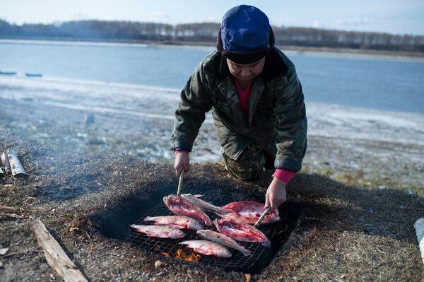 Ojciec Ajdara Kołdaszewa Hanid wędzi rybę, którą pojmał wraz z synem - Sputnik Polska