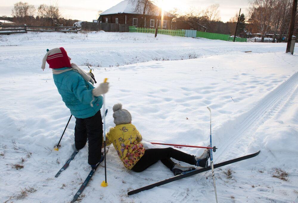 Dzieci jeżdżą na nartach w zaśnieżonej wsi Bieriozowka w obwodzie tomskim