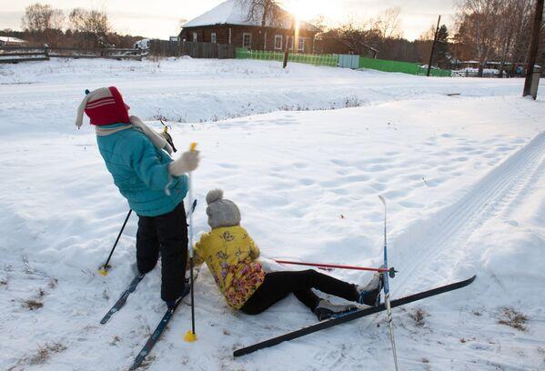 Dzieci jeżdżą na nartach w zaśnieżonej wsi Bieriozowka w obwodzie tomskim - Sputnik Polska