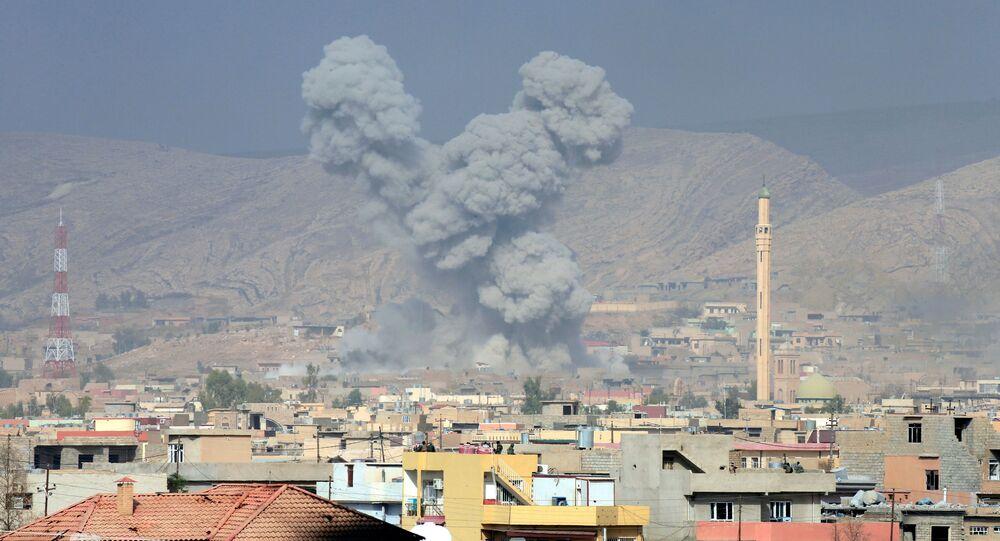 Dym nad domami w mieście Ba`shiqah na południe od Mosulu w Iraku