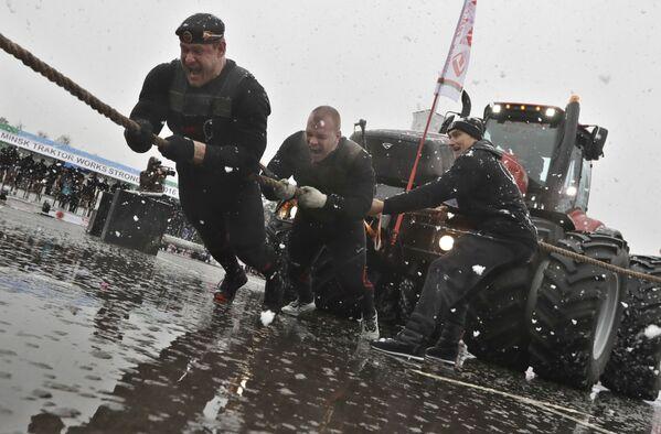 Białoruski sportowiec Dmitrij Belaic i Rosjanin Michaił Szewljakow ciągną nowy model traktoru Belorusy 4522 podczas jego prezentacji w Mińsku - Sputnik Polska