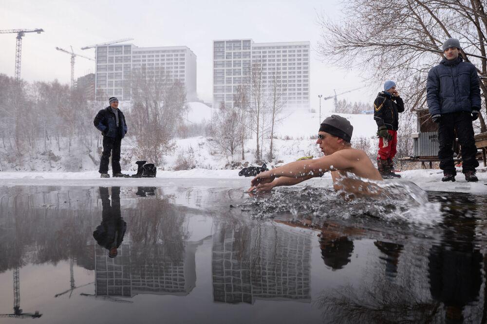 Wielbiciele pływania zimowego z klubu Spektr kąpią się w przeręblu w jeziorze Bliudce w Nowosybirsku