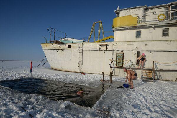 Wielbiciele pływania zimowego z klubu Spektr kąpią się w przeręblu w jeziorze Bliudce w Nowosybirsku - Sputnik Polska
