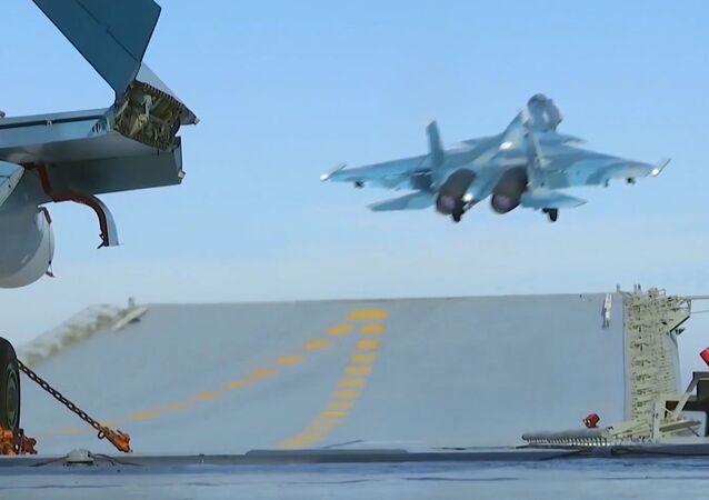 """Myśliwiec Su-33 ląduje na pokładzie ciężkiego krążownika lotniskowego """"Admirał Floty Związku Radzieckiego Kuzniecow"""" u brzegów Syrii"""