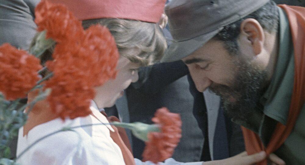 Pionera soviética cuelga un pañuelo rojo (símbolo de los pioneros) en el cuello de Fidel Castro.
