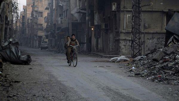 Chłopcy jadą rowerem zniszczonymi ulicami syryjskiego miasta Dajr az-Zaur - Sputnik Polska