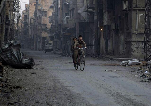 Chłopcy jadą rowerem zniszczonymi ulicami syryjskiego miasta Dajr az-Zaur