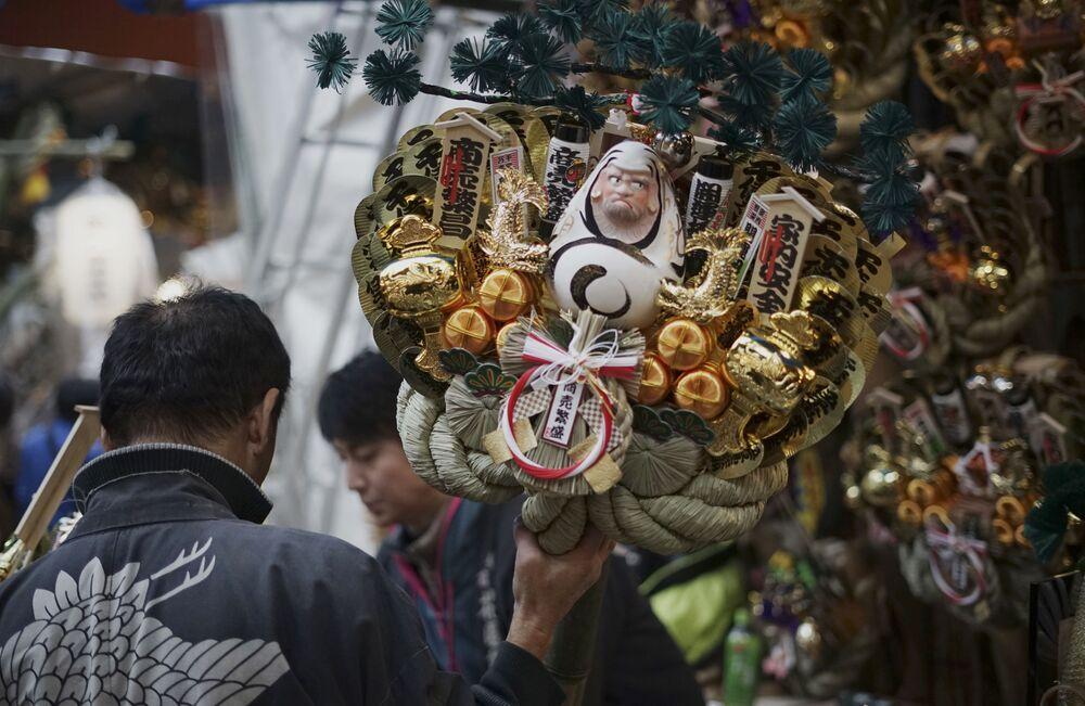 Sprzedawca japońskiej maskotki w postaci grabi Kumade w Tokio