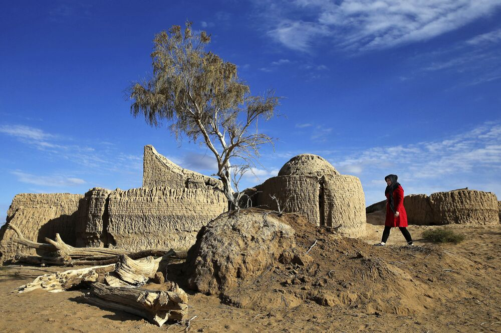 Kobieta spaceruje wśród ruin na pustyni Mesr w Iranie