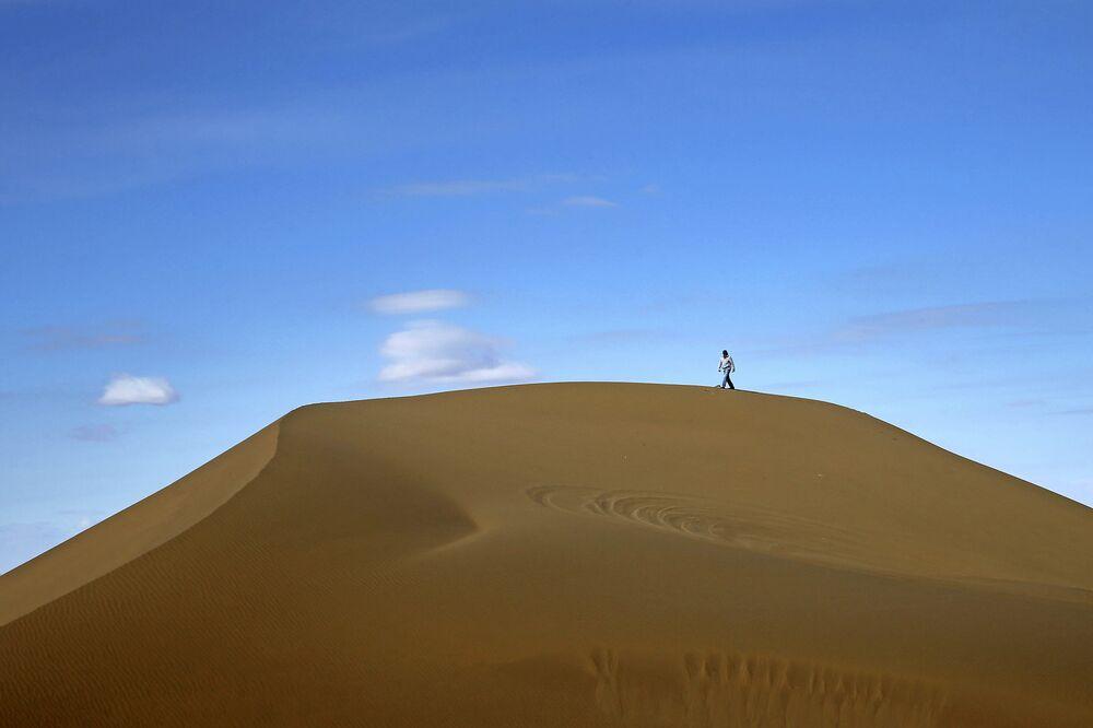 Mężczyzna spaceruje po pustyni Mesr w Iranie