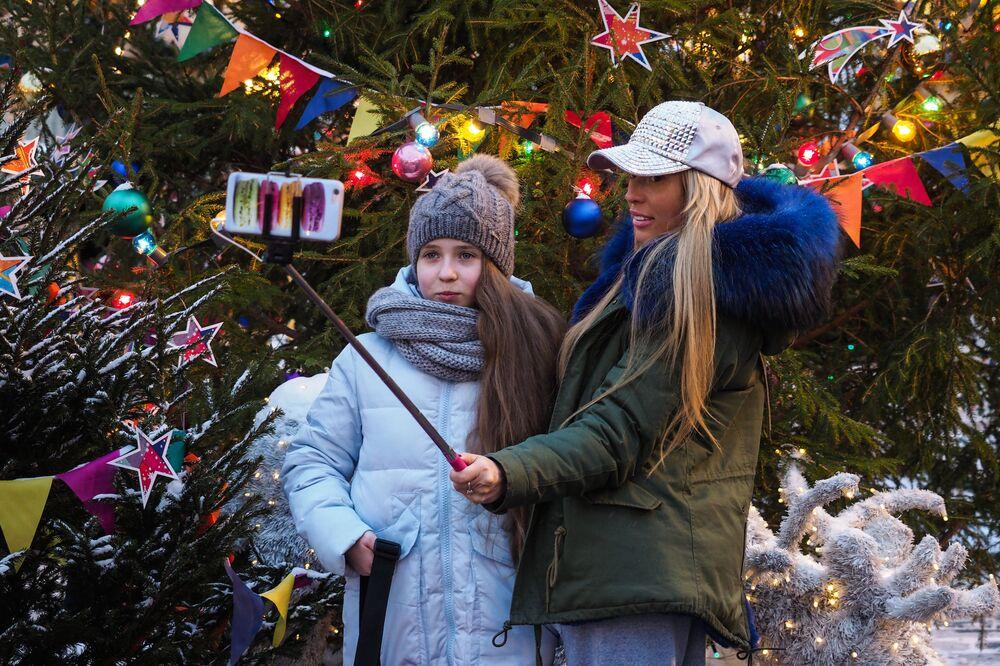 Mama z córka robią selfie przy choince noworocznej na Placu Czerwonym w Moskwie
