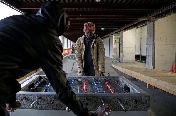 Migranci grają w piłkarzyki w ośrodku dla uchodźców w Paryżu - Sputnik Polska
