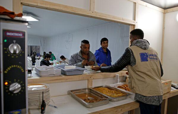 Wolontariusz rozdaje jedzenie w ośrodku dla uchodźców na północy Paryża - Sputnik Polska