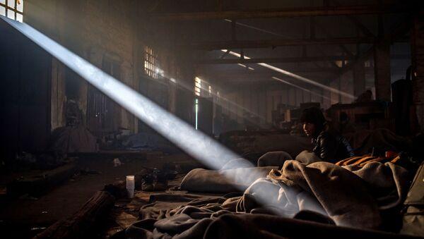 Uchodźca odpoczywa w prowizorycznym schronie w opuszczonym magazynie w Belgradzie - Sputnik Polska