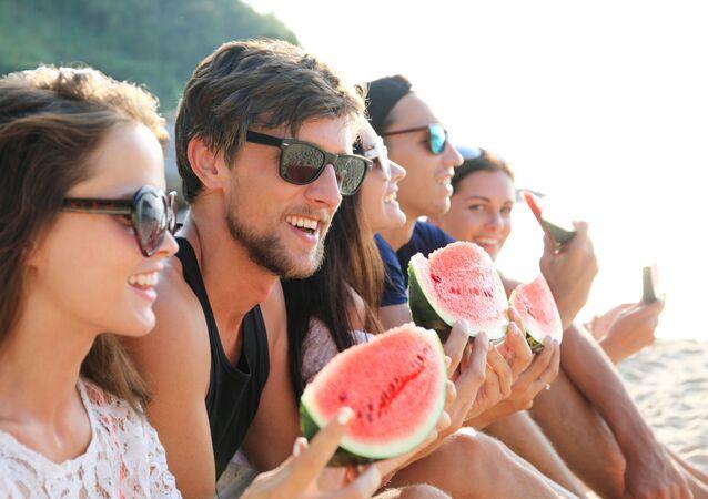 Młodzi ludzie jedzą arbuza na plaży