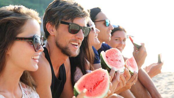 Młodzi ludzie jedzą arbuza na plaży - Sputnik Polska