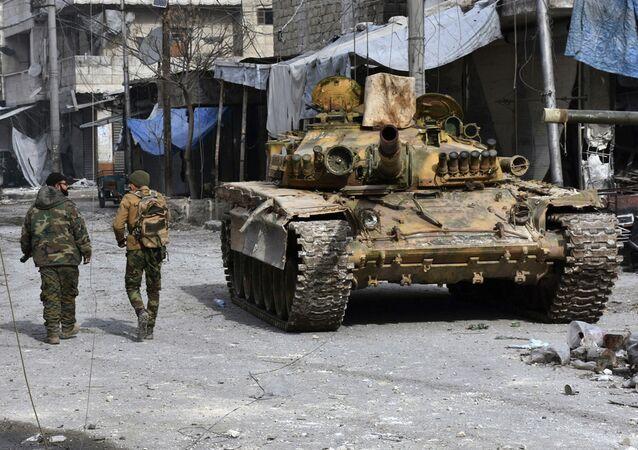 Dwóch syryjskich żołnierzy obok czołgu na wschodzie Aleppo