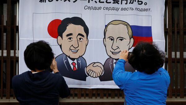 Ludzie fotografują plakat z podobizną prezydenta Rosji Władimira Putina i premiera Japonii Shinzo Abe w Nagato - Sputnik Polska