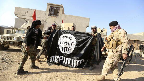 Iraccy wojskowi świętują odbicie wioski pod Mosulem z rąk PI, trzymając flagę pokonanych terrorystów - Sputnik Polska