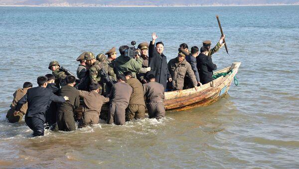 Kim Dzong Un macha z łódki - Sputnik Polska