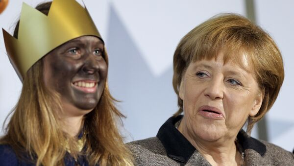 Angela Merkel z uczestniczką przedstawienia z okazji Święta Trzech Króli - Sputnik Polska