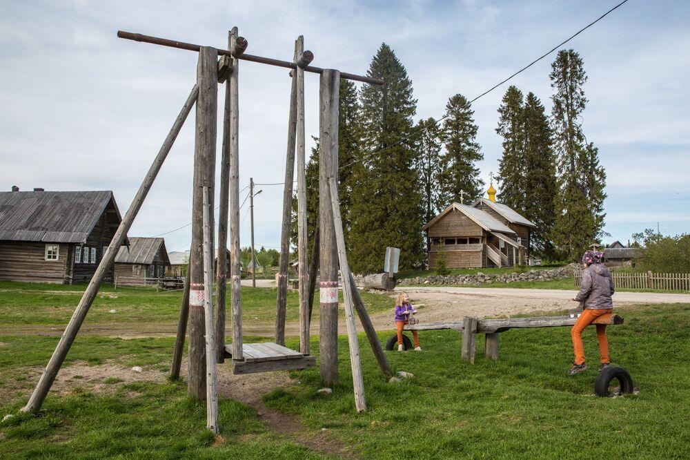 Dzieci bawiące się na placu zabaw we wsi Kinierma w Karelii. W 2016 roku wieś Kinierma otrzymała tytuł Najpiękniejsza wieś w Rosji. Na drugim planie, z prawej - czasownia Matki Bożej Smoleńskiej(koniec XVII - poczatek XVIII wieku).