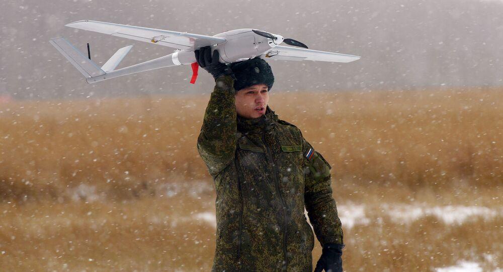 Elew trzyma w ręku dron Orłan-10 na poligonie w obwodzie moskiewskim