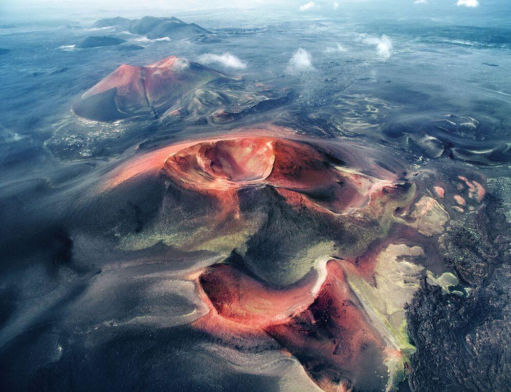 Kratery z lotu ptaka. Czerwone skały wyrastają spod warstwy czarnego popiołu, tworząc plastyczne wzory na powierzchni ziemi