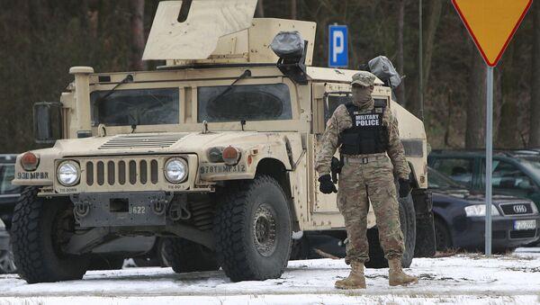 Amerykański wojskowy stoi obok pojazdu opancerzonego w Polsce - Sputnik Polska