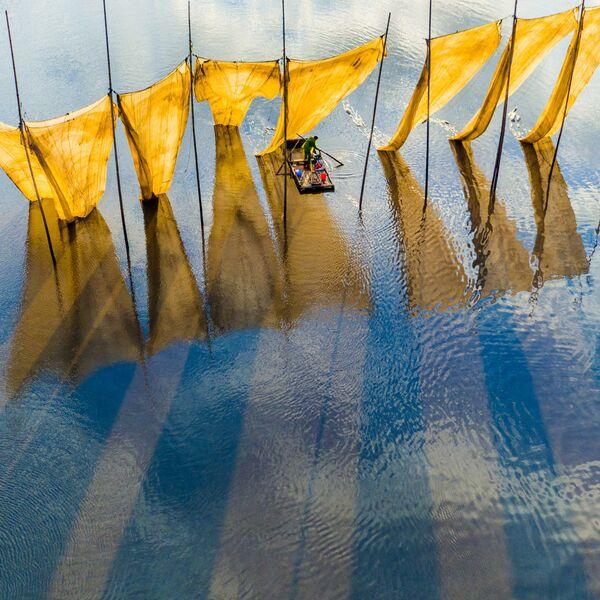 Główną nagrodę w konkursie otrzymał fotograf Ge Zheng za zdjęcie wędkarza zwijającego sieć. - Sputnik Polska