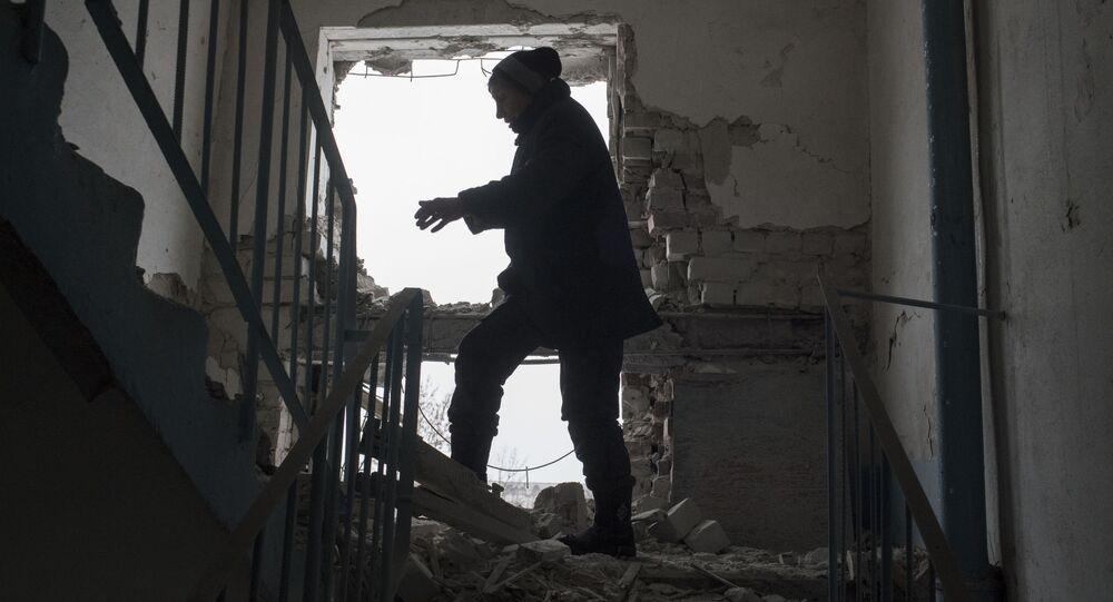 Mieszkaniec w uszkodzonym w wyniku ostrzałów budynku w dzielnicy Kijowska w Doniecku