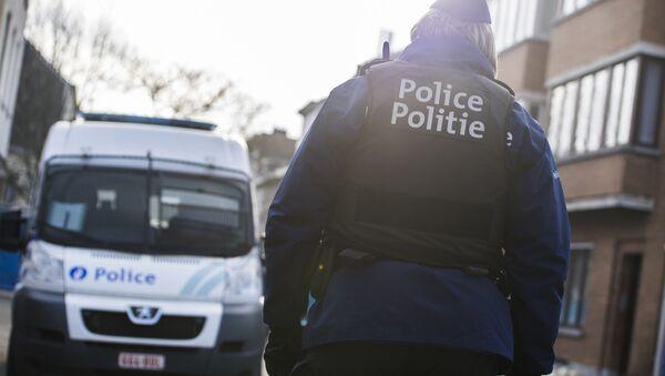 Oficer policji i samochód policyjny w Brukseli - Sputnik Polska