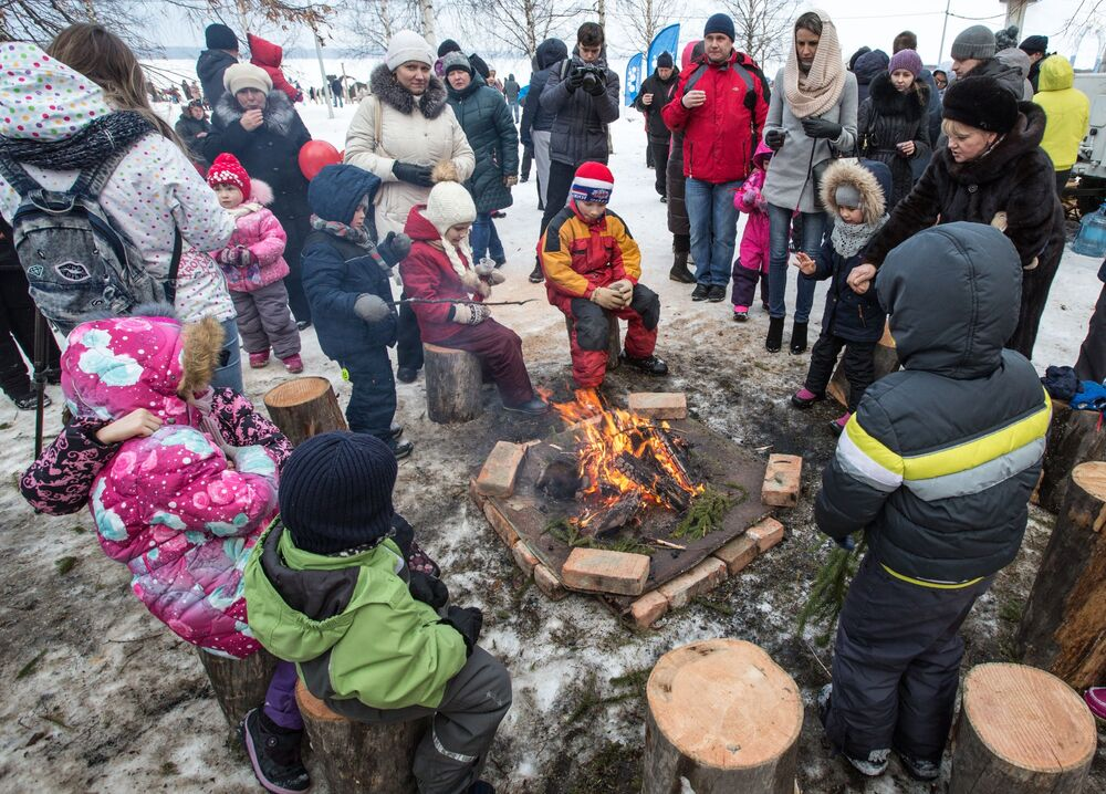 Mieszkańcy Karelii grzeją się przy ognisku podczas Międzynarodowego Zimowego Festiwalu Hiperborea w Karelii.