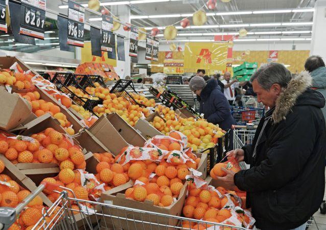 Посетитель выбирает фрукты в одном из магазинов торговой сети Ашан в Москве