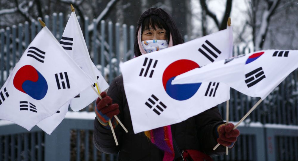 Kobieta trzyma flagi Korei Południowej podczas protestu przed ambasadą Korei Północnej w Berlinie
