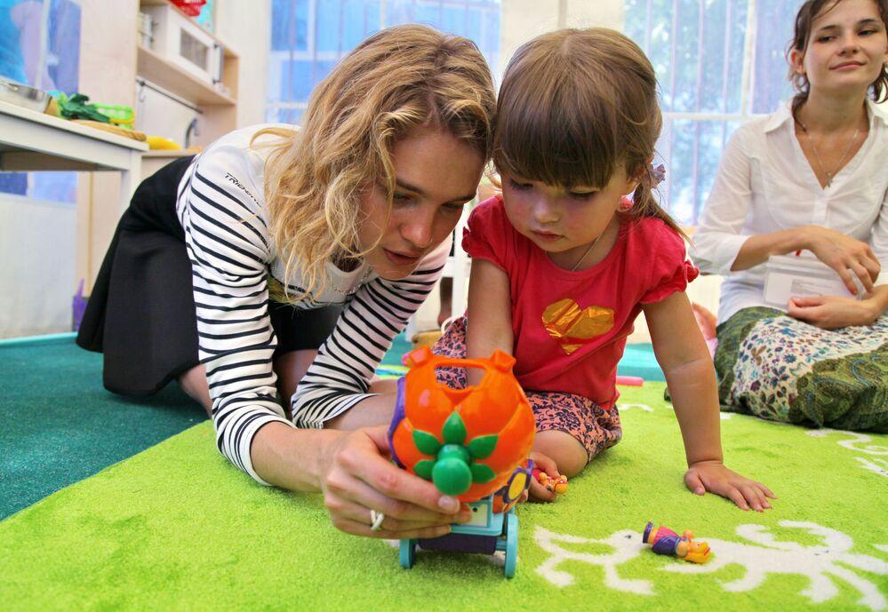 Modelka Natalia Vodianova bawi się z dzieckiem podczas otwarcia placu zabaw w ramach jej wizyty charytatywnej w Krymsku.