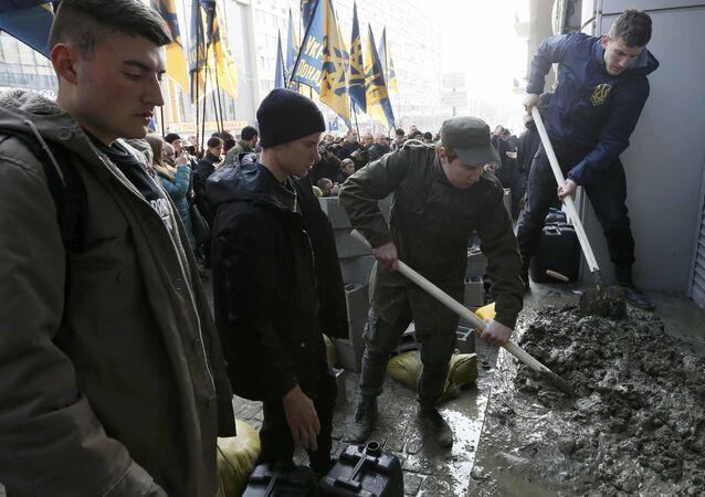 Członkowie ukraińskiej partii Korpus Narodowy zastawiają betonowymi blokami wejście do biura ukraińskiej córki Sbierbanku w Kijowie