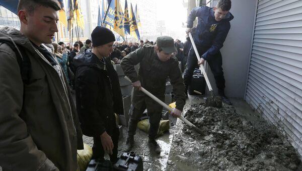 Członkowie ukraińskiej partii Korpus Narodowy zastawiają betonowymi blokami wejście do biura ukraińskiej córki Sbierbanku w Kijowie - Sputnik Polska